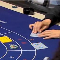 Un joueur plie la carte de baccarat dans un casino de Macao