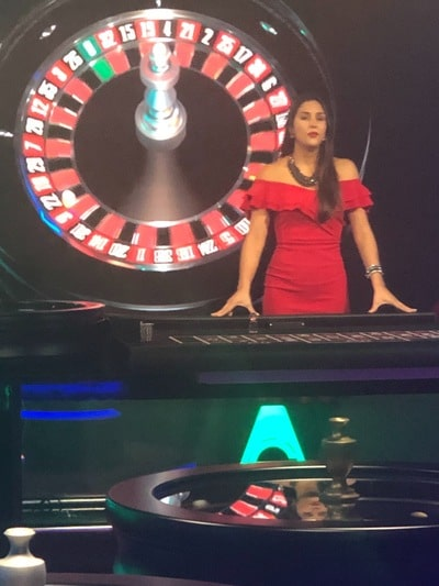 Croupière en action sur une table de roulette en ligne Authentic Gaming